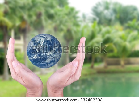 Human hand holding the blue Earth with blur the background of green trees. Elements of this image furnished by NASA. - stock photo