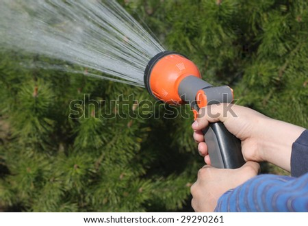 Human hand holding water sprinkler and watering green garden - stock photo