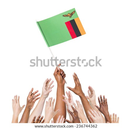 Human hand holding Zanbia Flag among multi-ethnic group of people's hand - stock photo