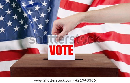 Human hand inserting bulletin in ballot box on USA National Flag background - stock photo