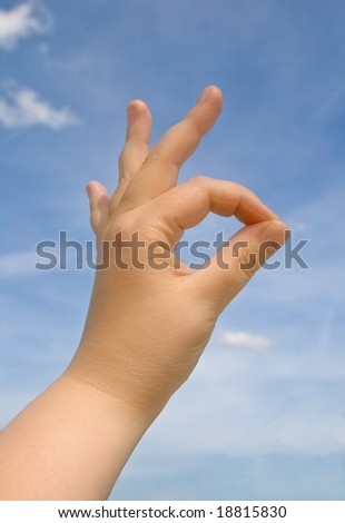 Human hand making OK sign against blue sky - stock photo