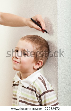 Human hand measure little child boy height growth - stock photo