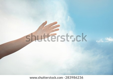 Human hand on a summer sky background - stock photo