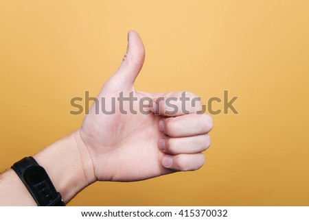 Human hand on a yellow background shows class, thumb up