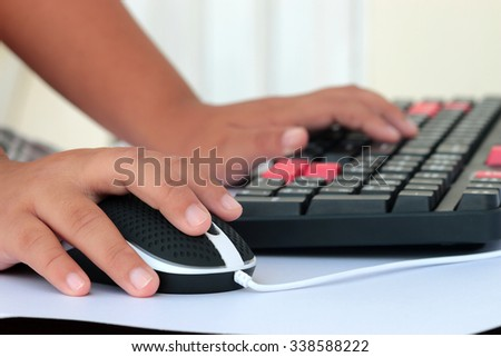 Human hand on computer mouse and keyboard on desk, focus hand on mouse