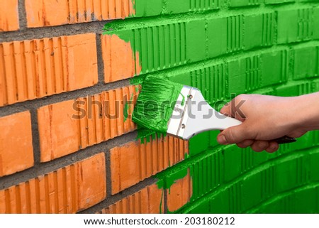 Human hand painting the wall with green color - stock photo
