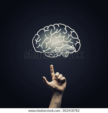 Human hand pointing with finger at brain icon - stock photo