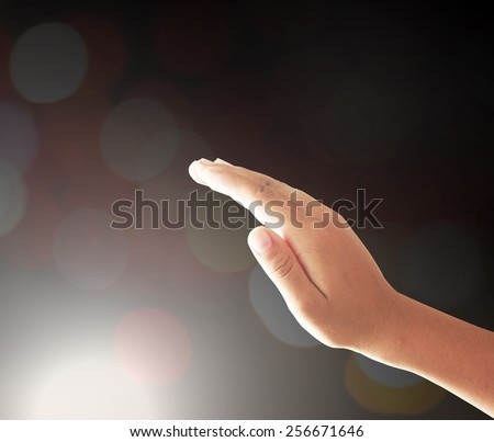 Human hand praying to other people over night light background.  - stock photo