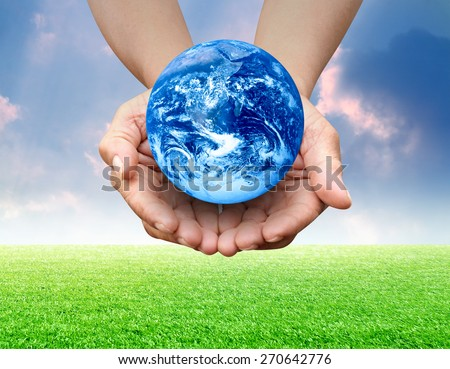 Human hand presenting global earth over blue sky and green grass field Elements of this image furnished by NASA - stock photo