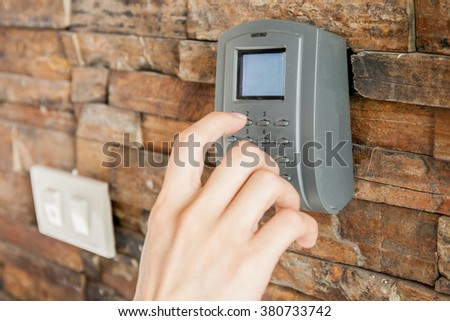 Human hand pressing on security combination code to unlock for entering the room - stock photo