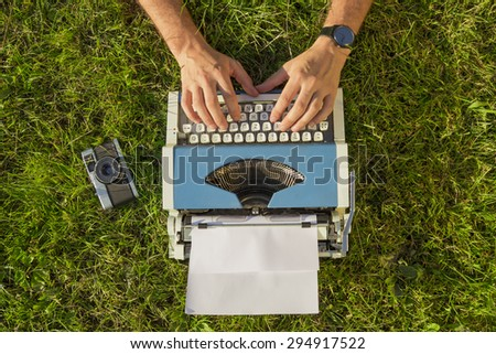 Human hand prints on retro typewriter in the grass - stock photo