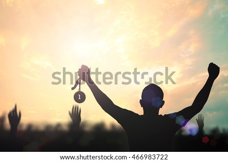 Human hand raised, holding gold medal against sky. Arm Win Goal First Moon Photo Prize Best Match Olympic Hero Metal Cloud Sun Aim Red Orange Day Many Pride Crowd Banner Champ Badge Contest High Place