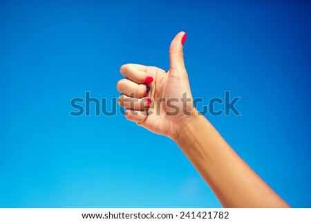 human hand showing thumb up with bright colorful nails - stock photo