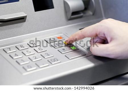 Human hand using ATM machine - stock photo