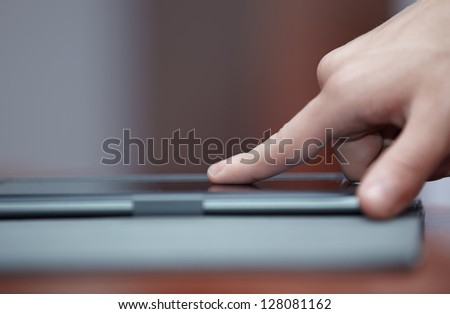 Human hand using tablet computer indoors - stock photo
