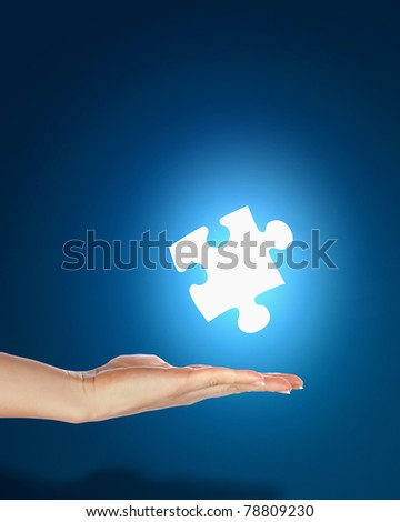 human hand with a blue shining piece of puzzle - stock photo