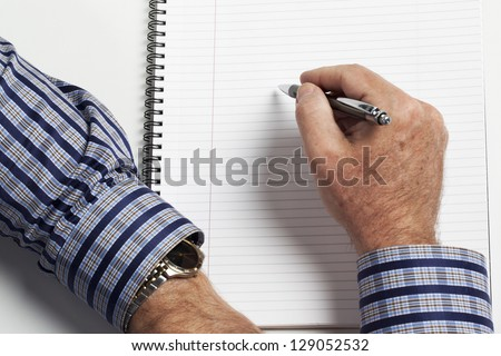 Human hand with book and pen over white background. - stock photo