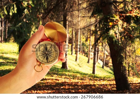 Human hand with compass on nature background - stock photo