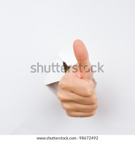 human hand with thumb up, coming out from a broken sheet of paper. - stock photo