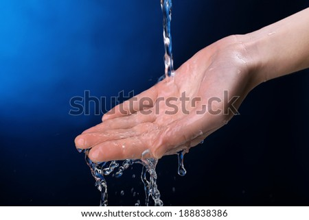 Human hand with water splashing on them on dark blue background