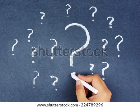 human hand writing question marks on blackboard - stock photo