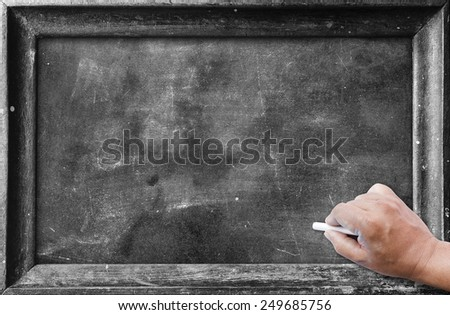 Human hand writing with chalk on blackboard. - stock photo