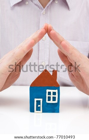 human hands covering  house made from plasticine. - stock photo