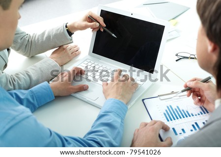 Human hands during discussion of new project on laptop - stock photo