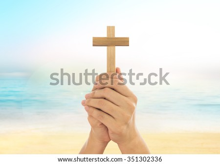 Human hands holding a cross holy and prayed for blessings from God. Amour Worship God concept. - stock photo