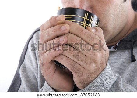 human hands holding a cup and drinking something warm supposedly - stock photo
