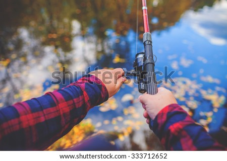 human hands holding a fishing-rod on the foreground - stock photo