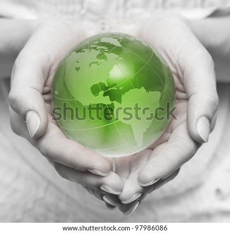 Human hands holding and take care about green planet . - stock photo