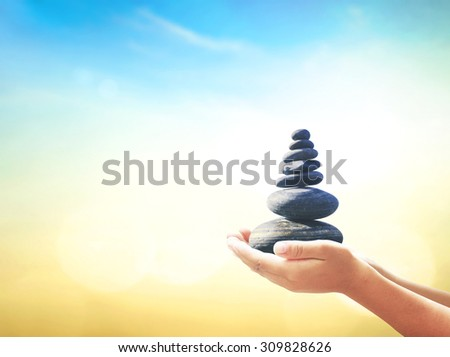 Human hands holding balanced seven Zen stones over blurred beautiful nature background. Ecology, Sustainability, World Philosophy Day, Business, Education, Religion, Wisdom, Autism Awareness concept - stock photo