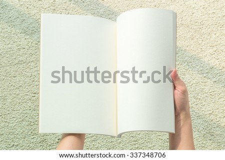 Human hands holding blank open book, catalog, magazines, brochure, note template with paper texture on blur light cream color carpet floor background with light shadow: Empty note pages from top view  - stock photo
