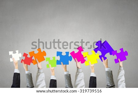 Human hands holding colorful jigsaw puzzle elements