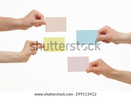 Human hands holding colorful paper cards on white background