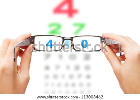 Human hands holding eyeglasses with eye chart in the back
