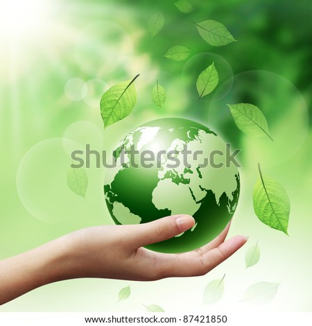 human hands holding green earth with a leaf
