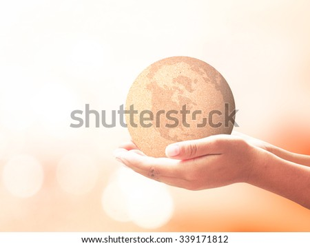 Human hands holding paper world ball. Paper in human hand over blurred orange autumn nature background. E-learning, Education, Internet Library Charity Donation Environment Day Globe Map concept.  - stock photo