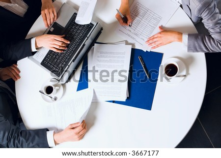 Human hands holding pens and papers, making notes in documents, typing on the lap top placed on the table with two cups of coffee on it