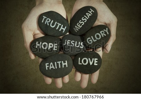 Human hands holding stones with keywords about jesus - stock photo