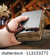 human hands holding the Bible and praying with a rosary - stock photo
