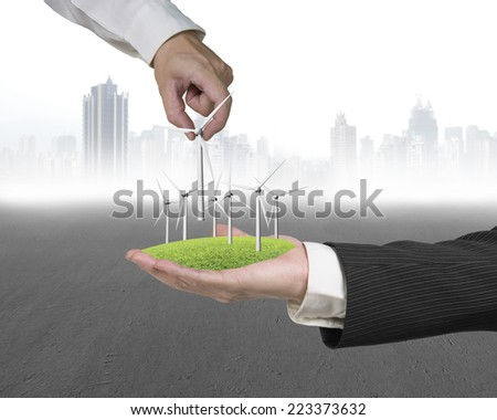 human hands holding windmills on grass with city buildings background - stock photo