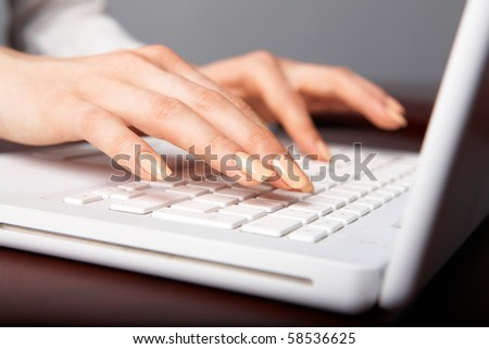 Human hands over laptop keypad during typing