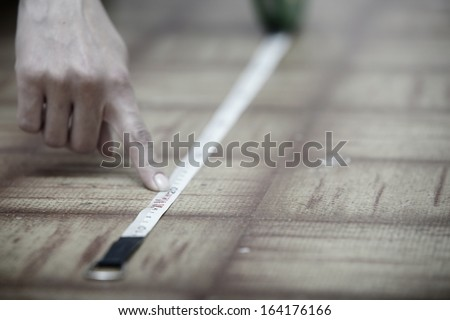 Human hands using measuring tape on a wooden surface