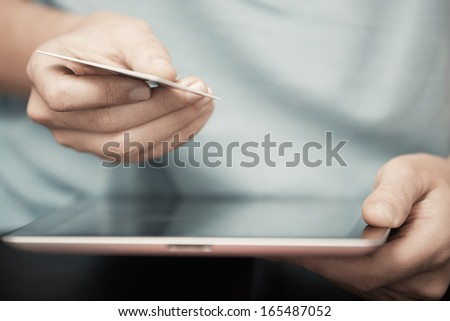 Human hands with digital tablet and credit card - stock photo