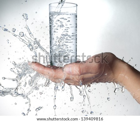 human hands with glass and water splashing on them - stock photo