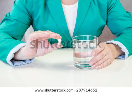 human hands with pill and glass of water