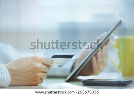 Human hands with tablet PC and credit card behind the office glass - stock photo