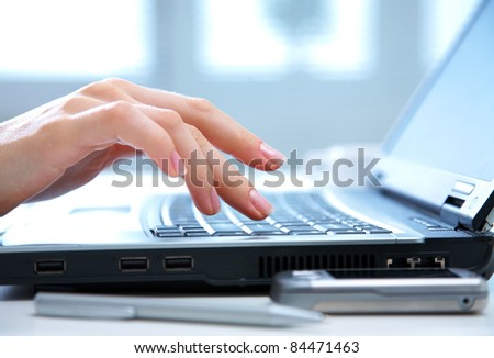 Human hands working on laptop on office background - stock photo